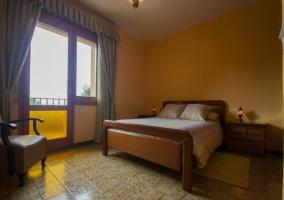 Dormitorio con terraza y cama de matrimonio