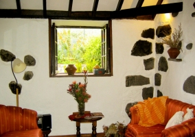 Sillones naranjas con paredes blancas y de piedra