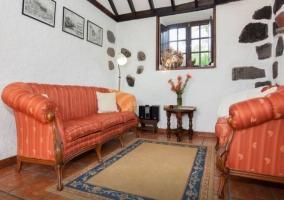 hall blanco con piedra vista y sofa naranja