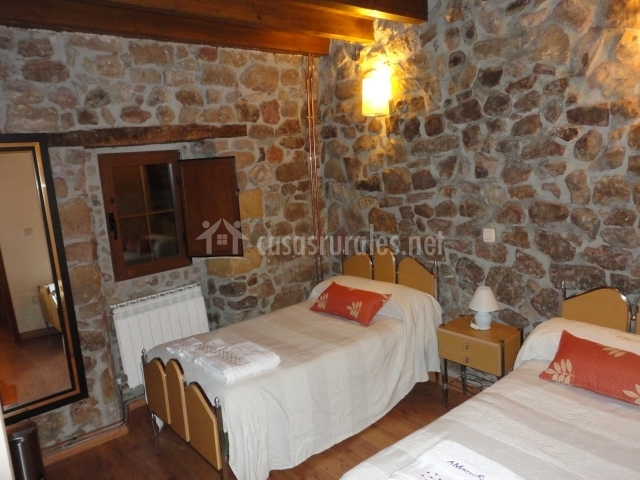 Habitación camas grandes y pared de piedra