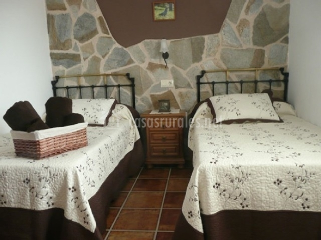 Dormitorio con dos camas individuales en tonos marrones y pared decorada con piedra