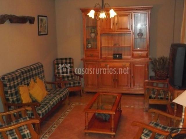 Sala de estar con sillones de cuadros y mueble de madera