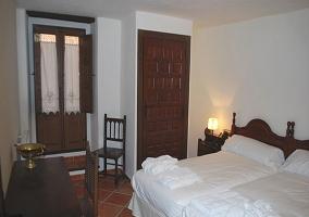Habitación doble con muebles de madera y tonos blancos