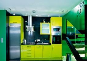 Cocina con muebles verde pistacho junto a las escaleras