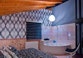 Habitación con televisión en la pared junto a la bañera