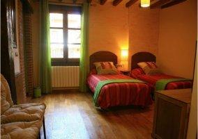 Habitación con 2 camas y 1 mesita de la casa rural