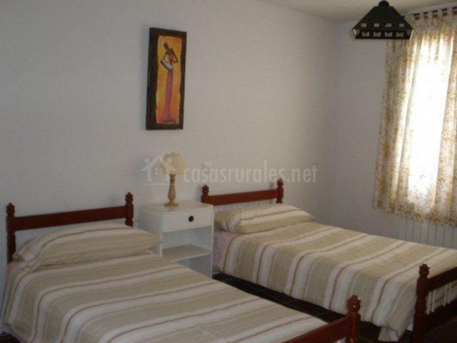 Dormitorio con camas individuales en color tierra y ventana