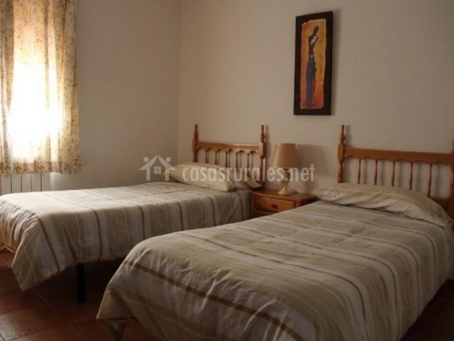 Dormitorio con camas individuales en color tierra