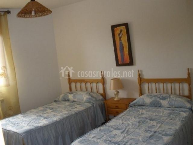 Dormitorio con camas individuales y ventana