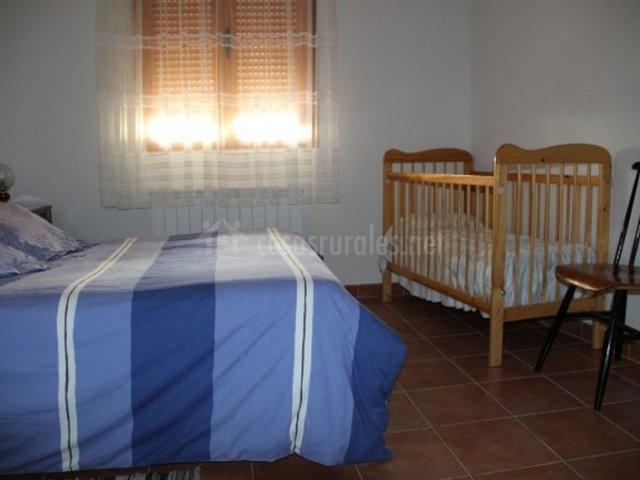 Dormitorio de matrimonio con colcha azul y cuna