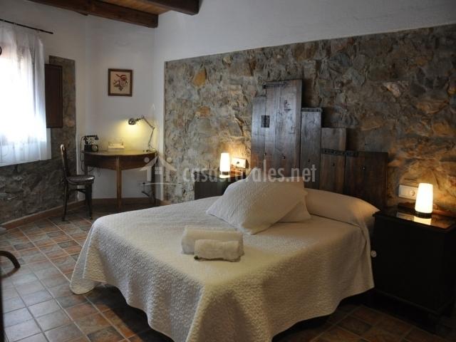 Habitación con cama matrimonial y cabecero de madera