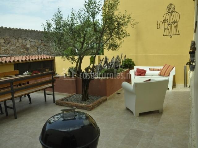 Terraza con barbacoa portátil, árbol y sofas