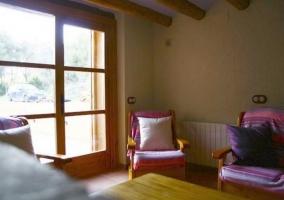 Sala de estar con mesa de madera y cocina al fondo