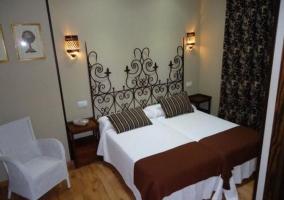 Dormitorio doble con cabecero de forja junto a butaca
