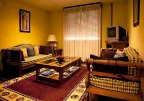 Salón con sillones, mesa y televisor