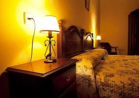 Dormitorio con dos camas y lamparilla encendida