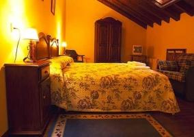 Dormitorio doble con camas, televisor y techo abuhardillado