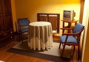 Zona de estar con mesa, sillas y televisor en dormitorio
