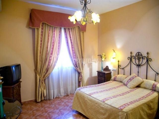 Dormitorio de matrimonio con televisor y gran ventana