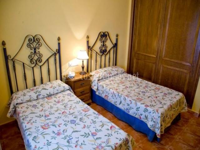 Dormitorio doble con camas individuales y mesilla en el centro