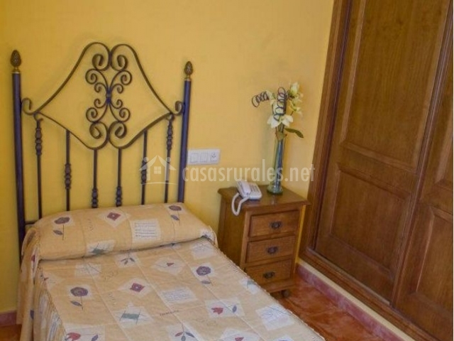 Dormitorio individual con mesilla de madera y armario