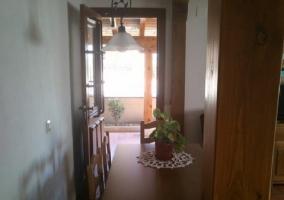 Sala de estar con sillón verde y mesa de comedor