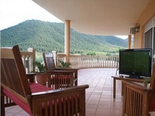 Amplia terraza techada con muebles de jardín