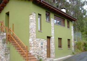 Fachada verde de la casa rural con detalles en piedra y escaleras exteriores