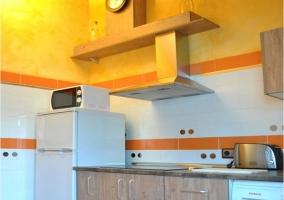 Cocina moderna con nevera, microondas y tostador