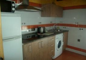 Cocina de la casa rural con azulejos blancos y cenefa naranja