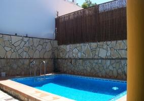 Muebles de exterior con sombrilla y barbacoa junto a la piscina