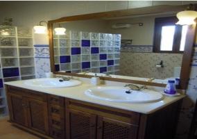 Baño con ducha y dos lavabos en habitación