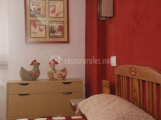 Dormitorio con pared roja y adornos