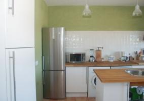Cocina con lavadora entre muebles bajos