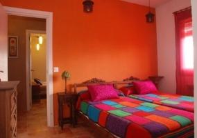 Dormitorio con paredes naranjas y dos camas