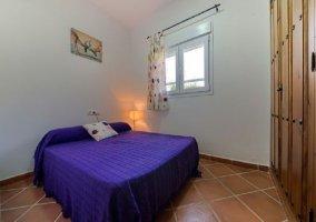 Dormitorio de matrimonio con cuadros y armario de madera