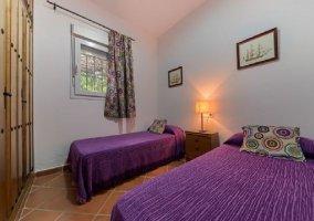 Dormitorio doble con colchas en morado