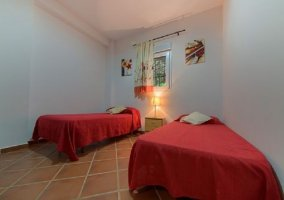 Dormitorio doble con colchas rojas