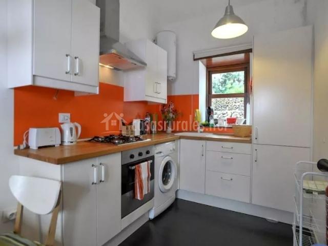 Cocina amplia en blanco y naranja