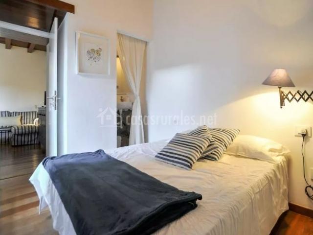 Dormitorio con manta en negro amplio y aseo