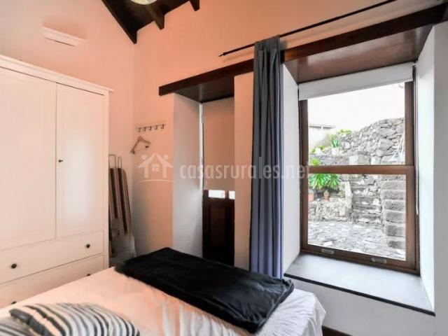 Dormitorio con manta en negro y ventana