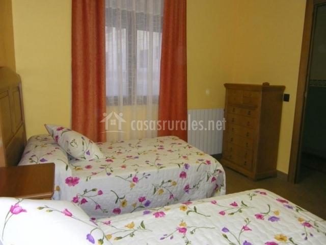 Dormitorio con dos camas individuales y cajonera delante