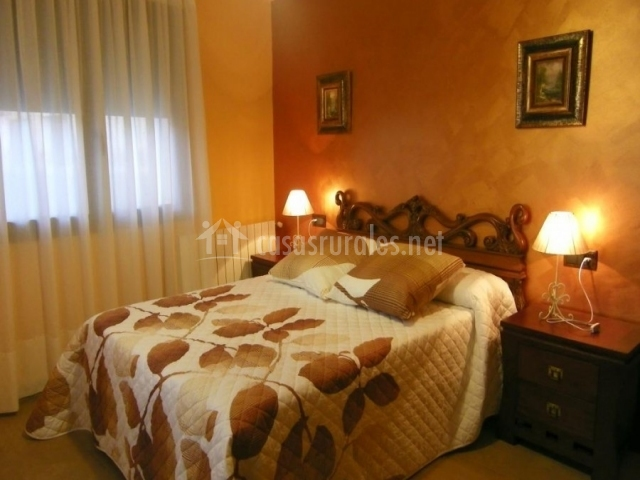 Dormitorio de matrimonio con la pared del cabacero marrón