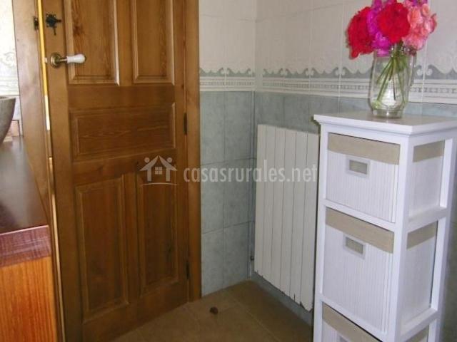 Mueble blanco con cajones frente al lavabo del aseo