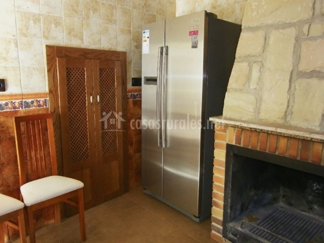 Nevera de dos puertas en la cocina junto a la chimenea y armario empotrado
