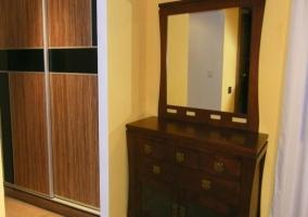 Cajonera con espejo junto a armario grande empotrado