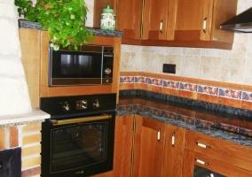 Cocina con encimera esquinada y horno bajo el microondas