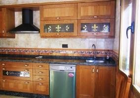 Cocina con muebles bajos y en la pared y lavavajillas