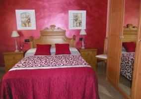 Dormitorio de matrimonio con armario y paredes rojas
