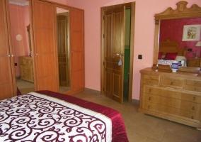 Dormitorio doble con cama de matrimonio y armario grande con espejos